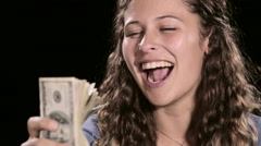 Young woman pumps her fist as she riffles through a wad of cash, shouting 'yes!' - stock footage