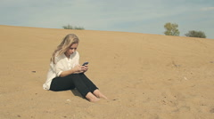Barefoot girl sitting on the sand with the phone Stock Footage