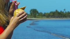 Panning shot of Woman drinking fresh coconut on the beach Stock Footage