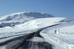 Snowy road in wintertime - stock photo