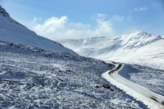 Snowy and icy road with volcanic mountains in wintertime - stock photo