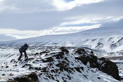 Photographer in wintry mountain landscape, Iceland - stock photo