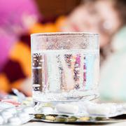 glass with dissolved drug in and pills on table - stock photo