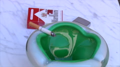 Ashtray with smoking cigarettes - stock footage