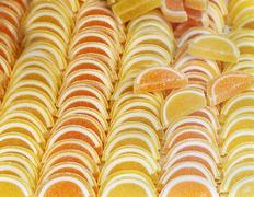 Stock Photo of Orange flavour jelly sweets pile with sprinkled sugar