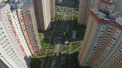 The road between buildings with riding cars. The camera goes down. Aerial view. Stock Footage