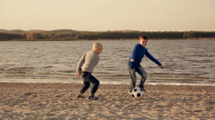 two little boys playing football on the beach - stock footage