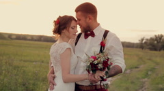 beautiful young couple bride and groom standing in the park at sunset and - stock footage