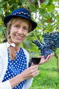 Woman holding glass of wine near bunch of blue grapes - stock photo