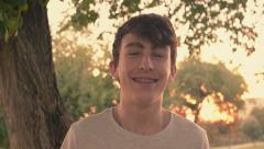 Portrait of happy, cheerful teenage boy laughing and looking at the camera Stock Footage