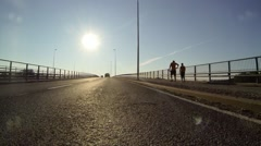 Bumper camera view of driving on a bridge with sun ahead Stock Footage