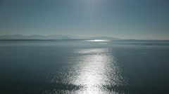 View of glistening and shimmering sea surface with hills on the horizon Stock Footage