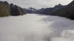 Aerial footage of mountains rising above the cloud line in the Southern Alps Stock Footage