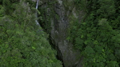 Aerial footage of the treetops and a mountain waterfall near Milford Sound - stock footage