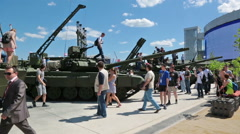 Visitors inspect armored vehicles at the exhibition - stock footage