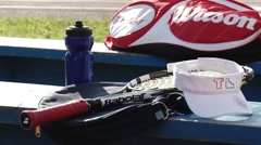 Tennis equipment. Cap, racket, carrying case, a bottle of water. Stock Footage