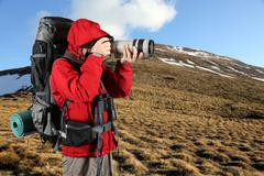 tourist in a red jacket with a gray backpack taking pictures - stock photo