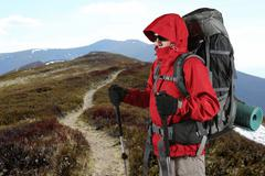 equipped with traveler in a red jacket stands on the hillside - stock photo
