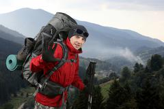 The happy traveler equipped with a red jacket on the hillside raised in greet Stock Photos