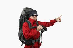 traveler with backpack red jacket with binoculars in hand on a white backgrou - stock photo