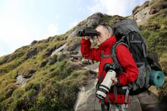 the equipped with the traveler photographer in the red jacket on the slope of - stock photo