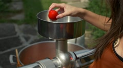 Woman places tomatoes in machine as man grinds pepper into large pot Stock Footage