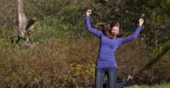 Woman leaping happily outdoors in smooth slow motion Stock Footage