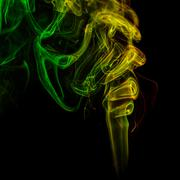 Abstract yellow and green smoke from the aromatic sticks. Stock Photos