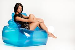 Young Woman On A Blue Inflatable Armchair - stock photo