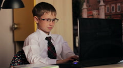 A boy with glasses, working on laptop computer. The young man knows how to Stock Footage