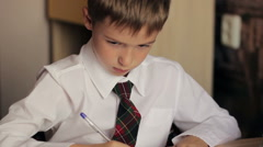 Little boy close-up of a schoolboy in a white shirt and tie is sitting at a Stock Footage