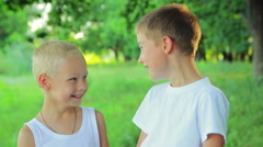 Two boys 8 years and 5 years in a white dress standing in the park looking at Stock Footage