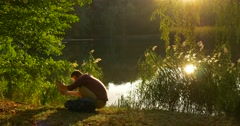 Man Sits to The Lake Bank Sitting on The Ground with Laptop Freelancer Stock Footage