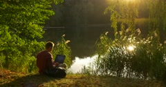 Man in Glasses is Working with Laptop Sitting at The Lake With His Face to the Stock Footage