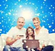 Happy family with laptop computer and credit card Stock Photos