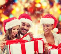 Happy family in santa hats sitting with gift boxes Stock Photos