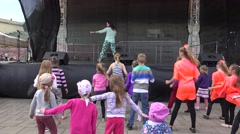 Woman show dance step on scene and children kids repeat it. 4K Stock Footage