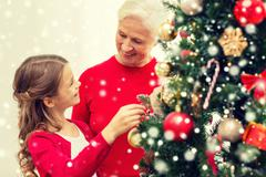 Stock Photo of smiling family decorating christmas tree at home