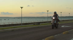 Young man in beige trench coat rides a scooter on a road next to sea at sunset - stock footage
