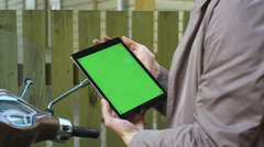 Young man in beige coat sits on a scooter and holds a tablet with green screen Stock Footage