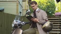 Young man in an elegant beige trench coat sits on a scooter and uses a tablet Stock Footage