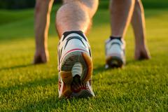 Runner feet running on grass. - stock photo