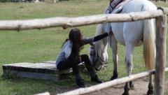 In rural school of horseback riding woman rider sit and rest by her white horse Stock Footage