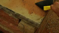 Archaeology archaeologist brushing off stone work Stock Footage