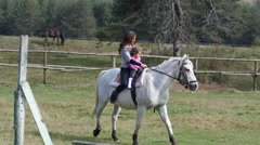 Mom rider teaches little child daughter girl riding a horse Stock Footage