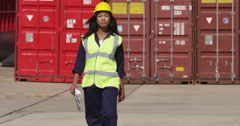 Portrait of a female dock worker at the harbor amidst shipping industry activity Stock Footage