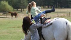 In a horseriding school woman rider helps a little girl climb on a horse Stock Footage