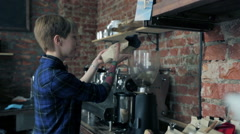 Cute girl barista added coffee beans in coffee grinder Stock Footage