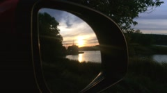 Sunset in car mirror. Forest and lake. - stock footage