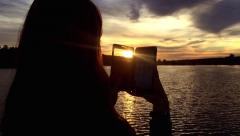 Girl make photo use big smartphone at sunset near lake. Stock Footage